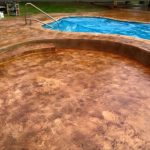 Beautiful stained concrete pool patio with built in seating and step